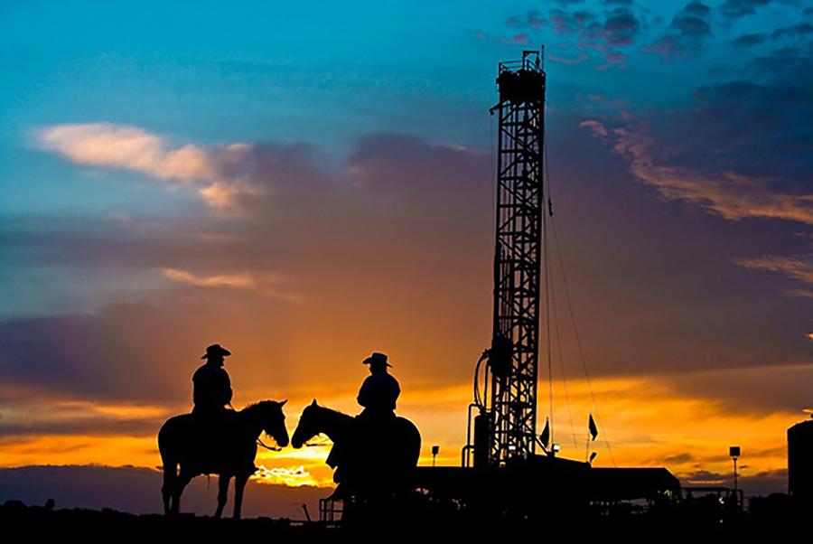 Two cowboys on horseback in front of an oil and gas drilling rig in the Eagle Ford Shale play at sunset in South Texas